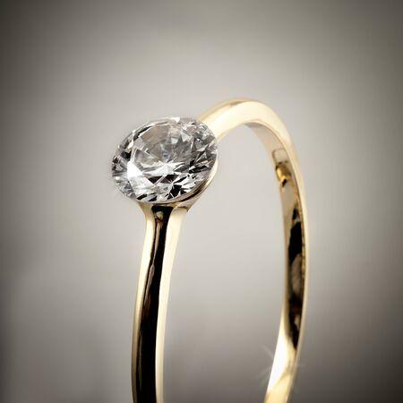 caras emociones: Cierre de anillo de compromiso de diamantes aislados sobre fondo gris