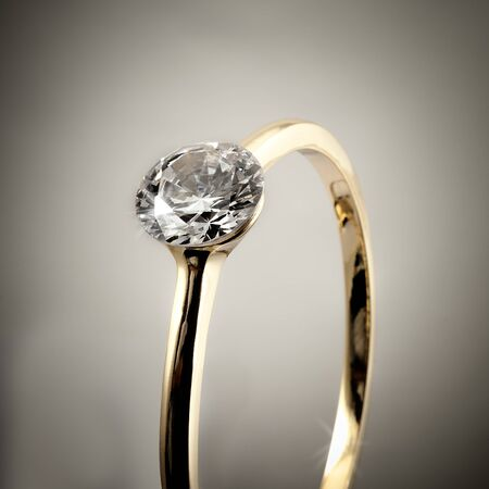 Close up of Diamond engagement ring isolated over gray background photo