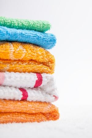 orange washcloth: Stacked colorful towels isolates over white Stock Photo