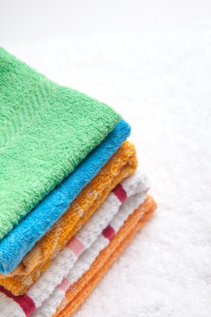 Stacked colorful towels isolates over white Stock Photo - 16931919