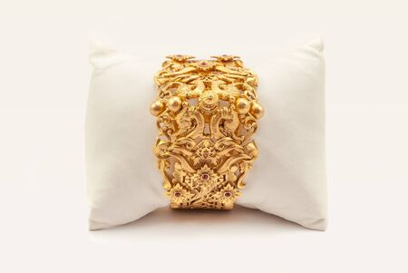 karat: Pure Gold  bracelet  having itself craft of gold looking historic over white background with soft cushion