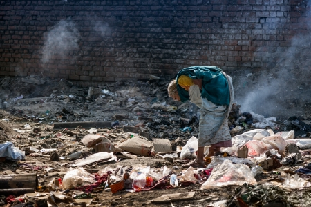 Pollution and poverty   Indian old female sitting  for warmup  herself near fire  in  garbage, photo