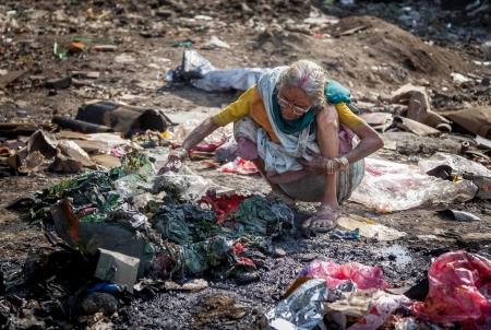 pobreza: La contaminación y la pobreza indios sesión edad las mujeres para sí misma calentamiento cerca del fuego en la basura,