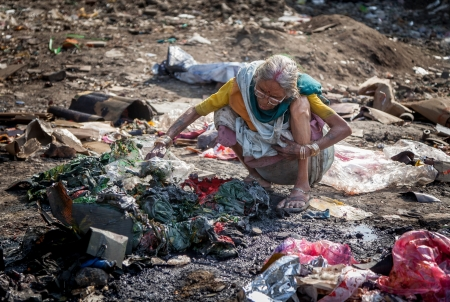 Pollution and poverty   Indian old female sitting  for warmup  herself near fire  in  garbage,