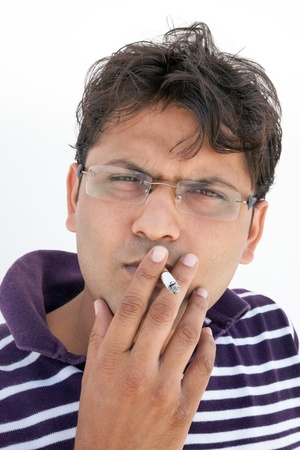 injurious: Close-up of an intensively smoking of indian man having spectacles