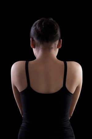 Back side of an asian woman in black dress on black background photo