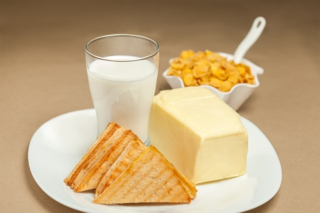 Milk, toast, butter and yellow cornflakes on breakfast table photo