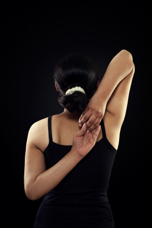 Indian girl in black dress trying to touch both hand from backside over on black background Stock Photo - 19793406