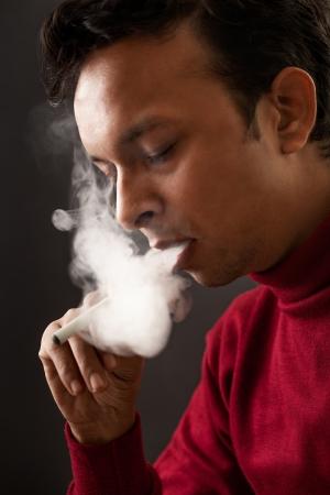electronic background: Smoking by indian man using electronic cigarette over gray background Stock Photo