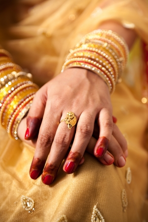 bride bangle: hand detail of indian bride with decorative bangle and gold ring