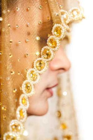 Traditional  happy Indian bride with a beautiful smile,  covered her face by veil photo