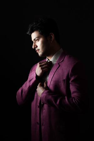 getting ready: Indian handsome man getting ready in purple party coat making knot of tie