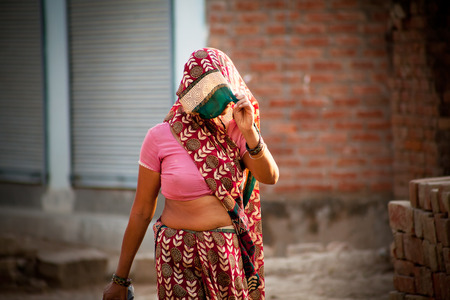 villager: Indian villager woman in veil with dark complexion going in summer noon Stock Photo