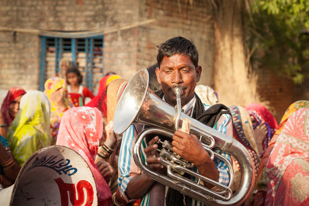 tuba: Indian local village marriage band performer playing trumpet or tuba in morning during party