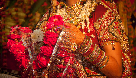 bangles hand: Garland of rose flower during hindu marriage in india Stock Photo