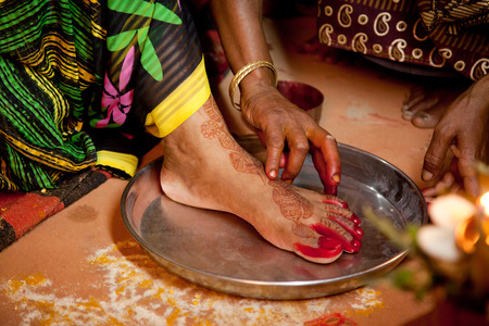 pooja: Indian bride doing marriage rituals doing colored foot fingure their mandap puja