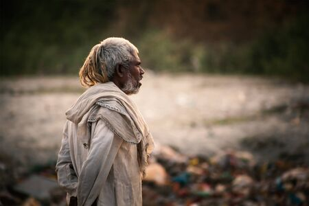 dirty old man: Portrait of poor old Indian man dressed in the old dirty cloths living in a shack Editorial