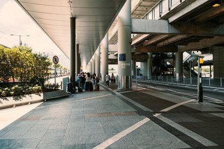 delays: People exiting or waiting outside airport,  Chek Lap Kok International Airport. Hong Kong SAR, 20 June, 2013