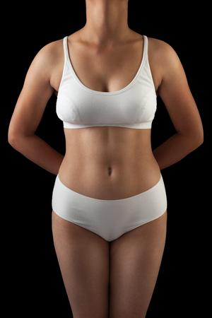 femme sous vetements: corps mince et sexy d'une jeune femme asiatique debout en soutien-gorge blanc et culotte isolé sur fond noir.