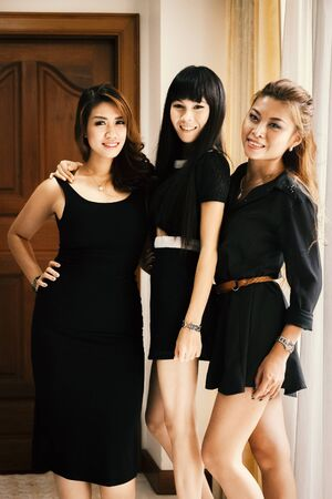 photo shoot: Beautiful happy young Asian Sexy women in black dresses standing and posing for photo shoot. Stock Photo