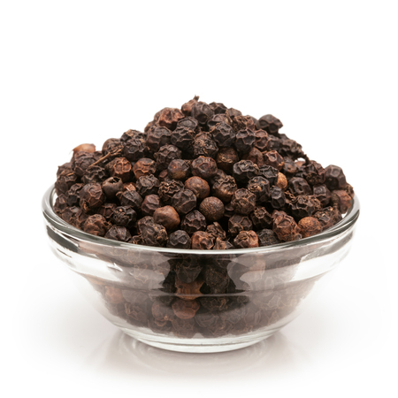 black pepper: Front view of Organic Black pepper Piper nigrum in glass bowl isolated on white background. Stock Photo