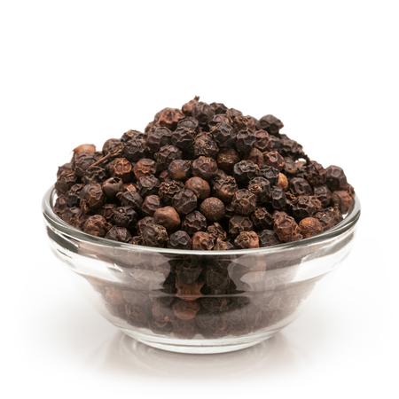 pepe nero: Vista frontale di Black organico pepe Piper nigrum in ciotola di vetro isolato su sfondo bianco.