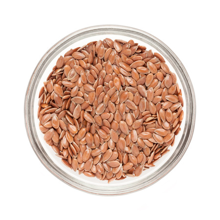 linum: Top view of Organic Linseed or Flaxseed Linum usitatissimum half filled in glass bowl isolated on white background.