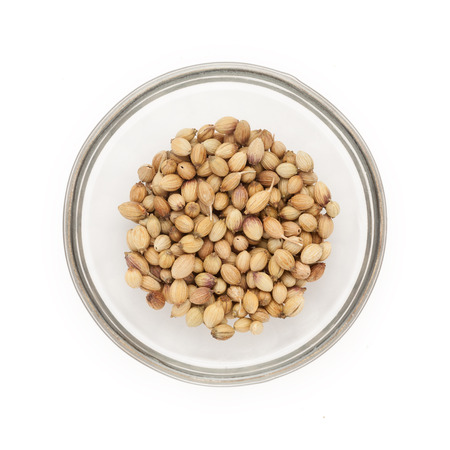 coriandrum sativum: Top view of Organic Dried coriander seeds Coriandrum sativum half filled in glass bowl isolated on white background. Stock Photo