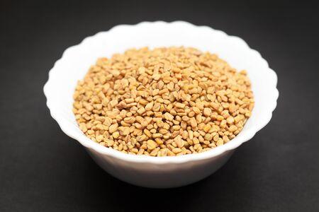 fenugreek: Organic Fenugreek Trigonella foenum-graecum in white ceramic bowl on dark background.