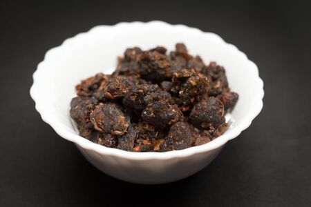 myrrh: Organic Indian bdellium or Guggul resin Commiphora wightii in white ceramic bowl on dark background.