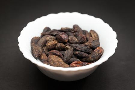 myrobalan: Organic Chebulic Myrobalan or Choti Harad Terminalia chebula in white ceramic bowl on dark background. Stock Photo
