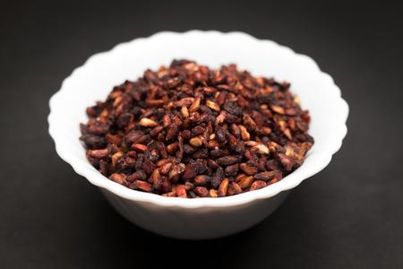 punica granatum: Organic Dried Pomegranate seeds Punica granatum in white ceramic bowl on dark background. Stock Photo