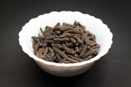 piper: Organic Long pepper Dried Fruit Piper longum in white ceramic bowl on dark background.
