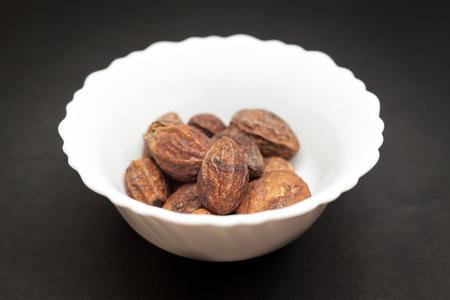 Organic Inknut or Harr Terminalia chebula in white ceramic bowl on dark background. Stok Fotoğraf - 47254984