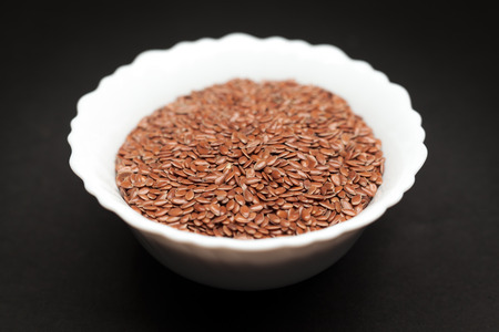 linum usitatissimum: Organic Linseed or Flaxseed Linum usitatissimum in white ceramic bowl on dark background. Stock Photo