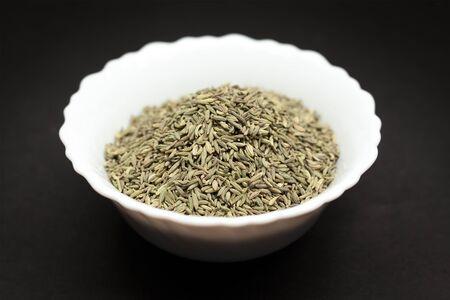 saunf: Organic Aniseed Pimpinella anisum in white ceramic bowl on dark background.