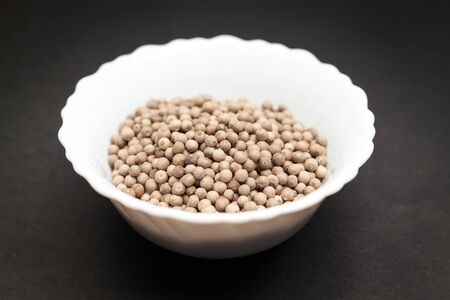 piperaceae: Organic White Pepper Piper nigrum in white ceramic bowl on dark background.