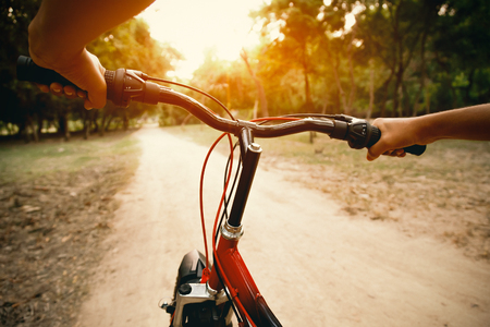 bicycles: Hands of a man on mountain bicycle handlebars in morning