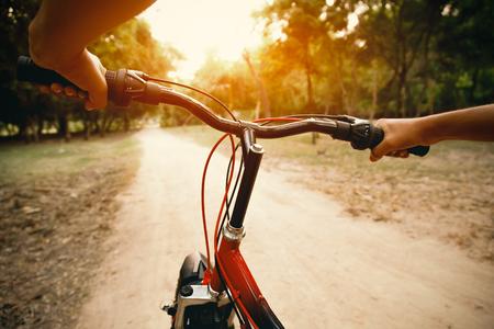 bicyclette: Mains d'un homme sur un guidon de vélo de montagne en matinée Banque d'images