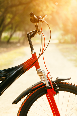 red mountain: Close up of front part of red and black mountain bicycle with morning sun. Stock Photo