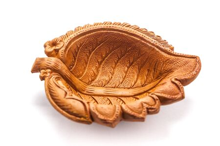 designe: Close up of a beautifully carved leaf designe handmade clay lamp isolated on white background. Stock Photo