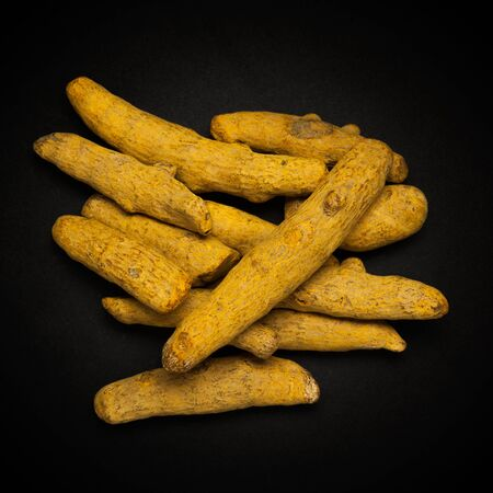curcuma: Top view of Organic Long Turmeric or Haldi Curcuma longa isolated on dark background.