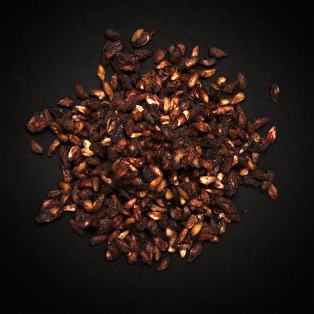 punica granatum: Top view of Organic Dried Pomegranate seeds Punica granatum isolated on dark background.