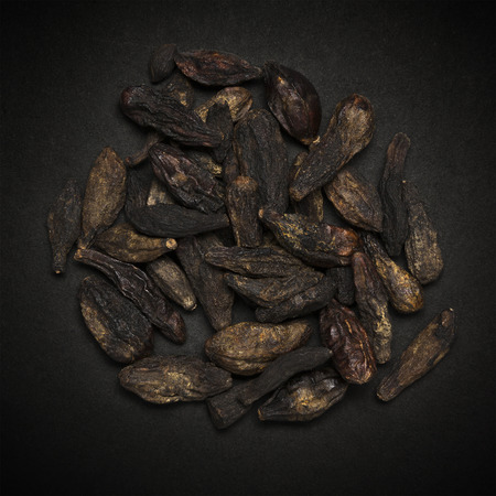 myrobalan: Top view of Organic Chebulic Myrobalan or Choti Harad Terminalia chebula isolated on dark background.