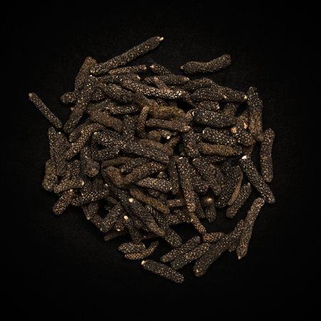 piper: Top view of Organic Long pepper Dried Fruit Piper longum isolated on dark background.