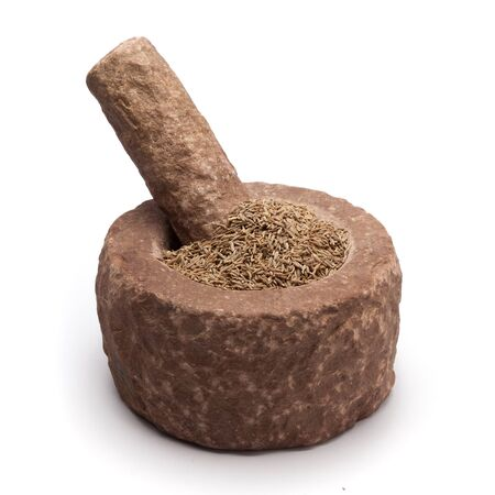 millstone: Organic Cumin seed Cuminum cyminum in mortar with pestle, isolated on white background. Stock Photo