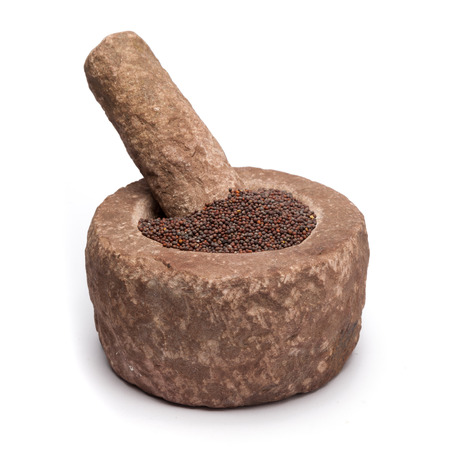 brassica: Organic brown mustard Brassica juncea in mortar with pestle, isolated on white background.