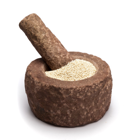 ajonjoli: Sésamo biológico blanco Sesamum indicum en el mortero con su correspondiente mano, aislados en fondo blanco.
