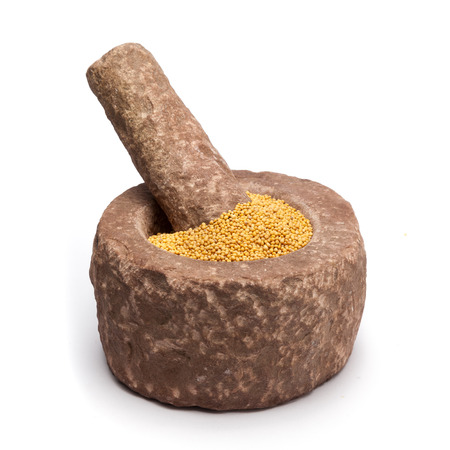 millstone: Organic yellow mustard Brassica alba in mortar with pestle, isolated on white background.