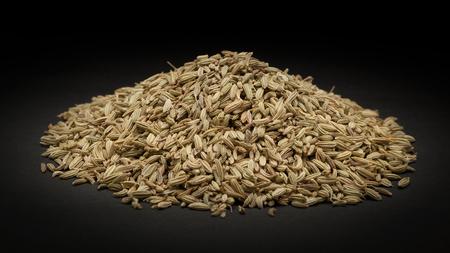 foeniculum vulgare: Pile of Organic Fennel seed Foeniculum Vulgare on dark background.